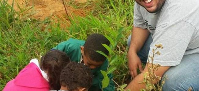 Secretário João Guilherme Ferreira no plantio com estudantes.