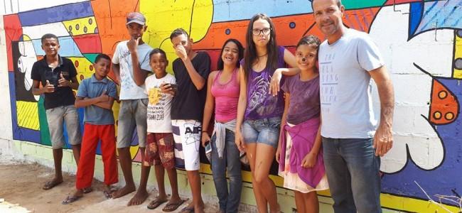 Paulinho Pintor e os estudantes, com a tela ao fundo.