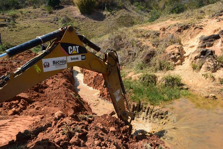Máquina trabalhando para levar água para manancial.